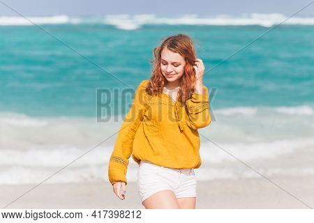 Beautiful Red Haired Teenage Girl Walking On The Ocean Coast In Dominican Republic