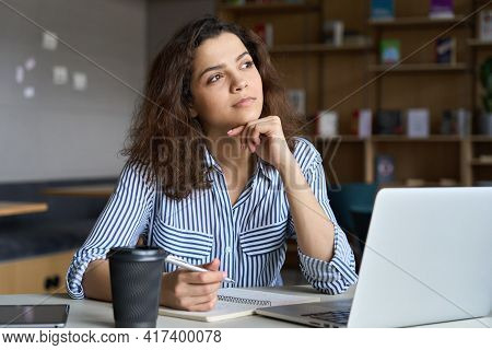 Young Indian Dreamy Thoughtful Student Looking Away Working On Laptop In Office Coworking Space Clas