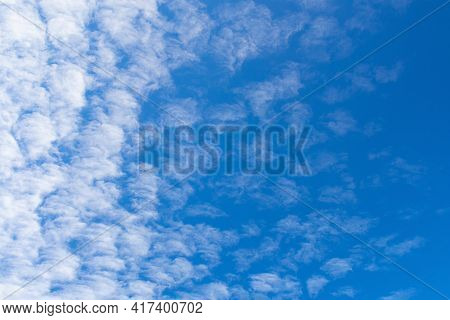 Blue Sky Background With Textured White Clouds On A Clear Day.