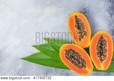 Ripe Papaya Halves On A Gray Marble Background With Green Leaves. Place For Your Text.