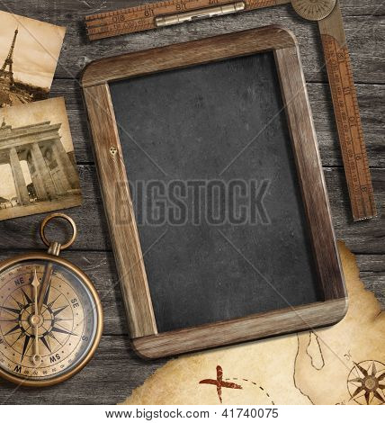 Vintage treasure map, blackboard with copyspace, old compass still life. Adventure or discovery concept.