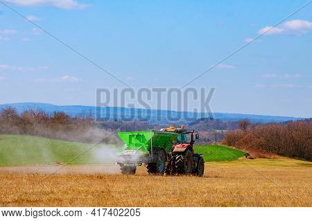 The Tractor Spreads Granular Fertilizer On A Grass Field. Agricultural Work. Mineral Fertilizers. Ni