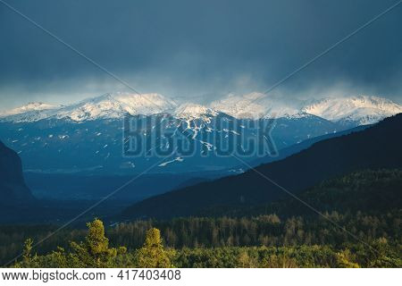 Sunlit Alpine Mountain Range With Snow Tops And Evergreen Forest During Stormy Weather In Inntal, Ti