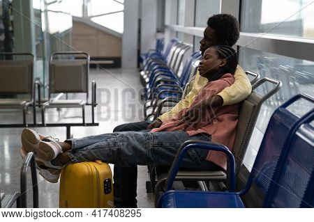 African Couple Sleeping On Chairs In Waiting Room Of Airport, Tired Wait For Delayed Flight. Black T