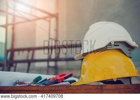 White Hard Hat On Yellow Hard Hat Construction Site Background