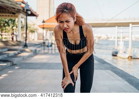 Young Asian Female Athlete Runner In Sportswear At River Side Suffering Pain And Discomfort From Kne