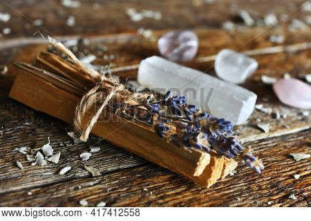 A Close Up Image Of Healing Smudge Sticks With Selenite And Clear Crystals On A Dark Wooden Table.