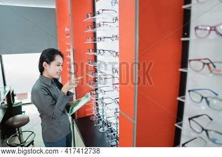 A Beautiful Woman Is Holding A Catalog Of Eyewear Products Available After She Has An Eye Check