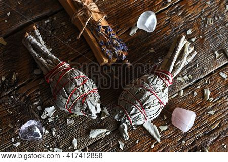A Top View Image Of Two Sage Smudge Sticks And Healing Crystals On A Dark Wooden Table Top.