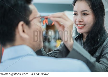 A Pretty Shop Clerk Helps Put New Glasses On To A Male Customer