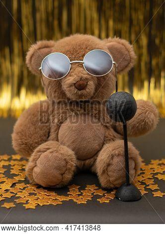Cute Teddy Bear With Sunglasses, A Microphone And Little Golden Stars On Black. Golden Curtain As Ba