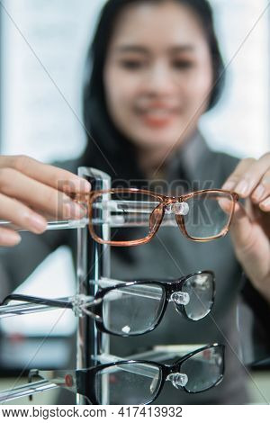 Selective Focus Of Eyeglass Frames Placed On A Shelf By A Woman Customer After Trying Them Out