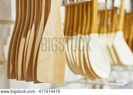 Shop Window With Wooden Kitchen Utensils. Cooking Spatulas Hang In Row. Sales Of Household Goods.