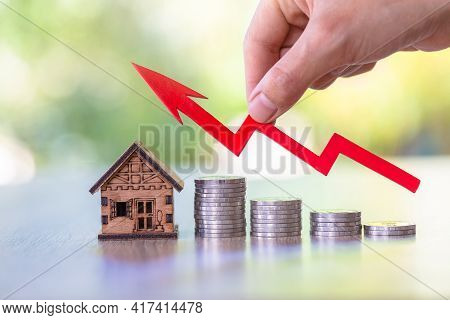 Hand  Holding Graph Over The Increasing House Miniature. Property Investment And House Mortgage Fina