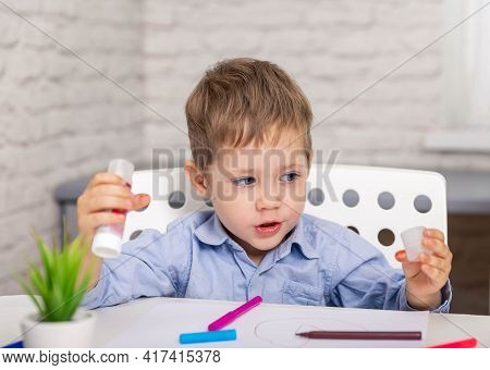 Getting Creative With Cutting. School Child Cutting Colored Paper With Scissors. Child Cutting Out S