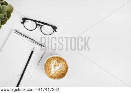 Office Table Desk, Workspace With Notebook, Pencil, Eyeglass. Coffee And Green Plant. Business Backg