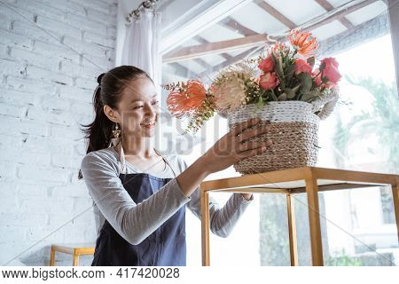 Happy Young Woman Florist Wearing Apron Tidying A Bucket Flower On Table