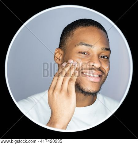 Man Skincare. Cosmetic Product. Selfcare Grooming. Portrait Of Satisfied African Guy Applying Face C