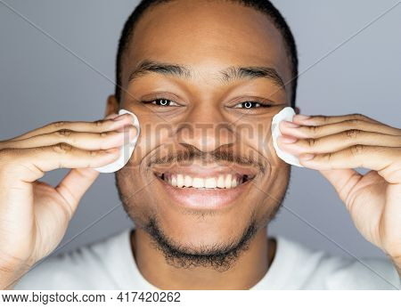 Man Skincare. Facial Cleansing. Acne Treatment Cosmetic Product. Cheerful African Guy With Perfect F