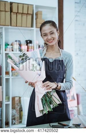 Happy Young Woman Florist Working In Flower Shop Holding Flannel Flower