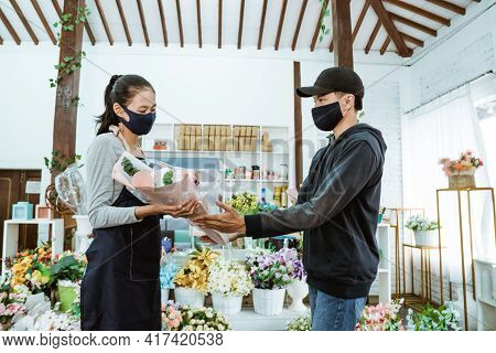Smiling Young Female Shopkeeper Wearing A Face Mask And Apron. Servicing Male Flannel Flower Buyers