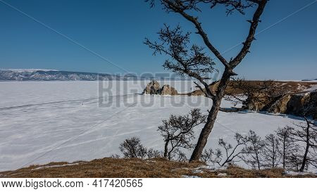 The Frozen Lake Is Covered With Snow. A Picturesque Two-headed Rock Rises Above The Surface. Trunks