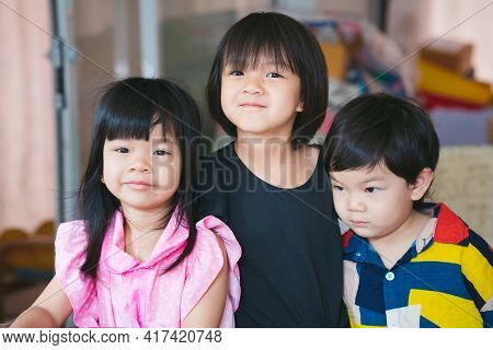 Three Sibling Held A Photo Together. Asian Cute Girl Smiles Sweetly, The Boy Does Not Look At The Ca
