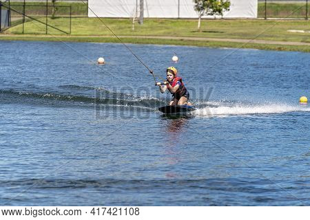 Mackay, Queensland, Australia - April 2021: A Young Girl Wearing A Safety Helmet And Life Jacket Enj