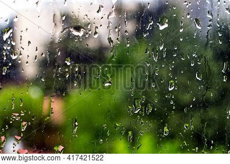 Rain Droplets On A Window Glass Pane With Green Trees On The Background. Selective Focus.