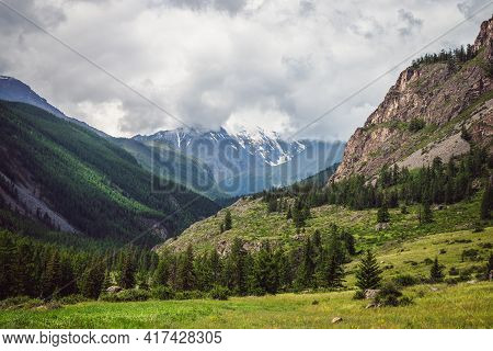 Dramatic Mountain Landscape With Green Forest In Sunlight And Snowy Mountains Among Rainy Low Clouds