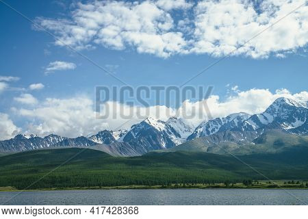 Awesome Landscape With Mountain Lake And Sunlit High Snowy Pinnacle Among Low Clouds In Blue Sky. At