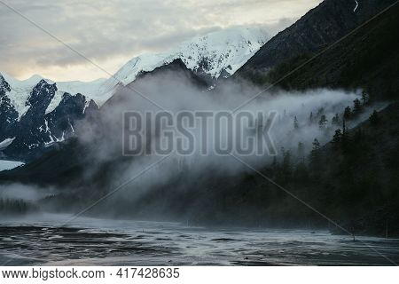 Atmospheric Landscape With Great Snowy Mountains On Sunset And Dense Low Clouds In Mountain Valley W