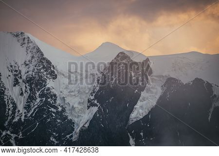 Minimal Alpine Landscape With Snowy Mountain Top Among Low Clouds On Background Of Sunset Or Sunrise