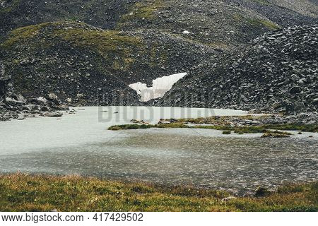 Bleak Rainy Landscape With Rain Circles On Water Surface Of Mountain Lake. Atmospheric Mountain Scen