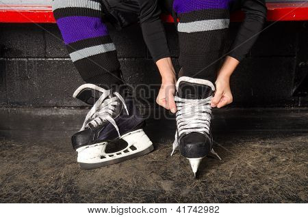 Child Tying Hockey Skates In Dressing Room