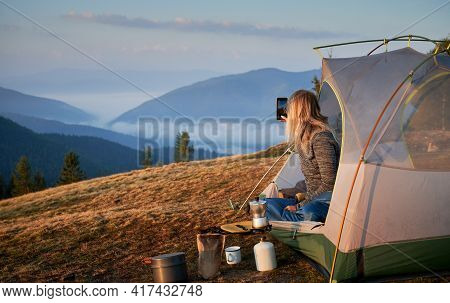 Rear View Of Girl Photographing Morning Landscape With Smartphone From Her Tent Set Up On Hill Durin