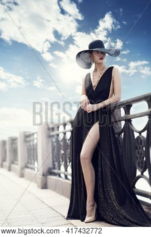 Fashion Woman In Hat And Black Dress Outdoor. Elegant Lady In Summer Hat Long Evening Gown In City P