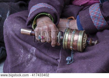 Old Tibetan Woman Holding Buddhist Prayer Wheel In Monastery, Ladakh, India, Close Up