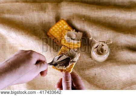 Close-up Of A Hand Spreading Pate On A Cracker With A Spoon. A Man Prepares Himself An Appetizer Wit