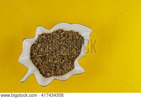 White Decorative Plate With Medicinal Herbs On A Yellow Background. Ceramic Plate In The Form Of A L