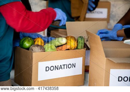 Group Of Unrecognizable Volunteers Busy Working By Arranging Vegetables And Clothes On Donation Boxe