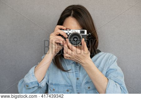 Front View Of Fashionable Nice Girl Taking A Picture With Retro Camera ,isolated On Grey Background