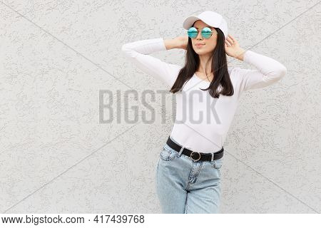 Portrait Of Beautiful Adult Woman With Perfect Body Raising Hands, Wearing Trendy Jeans, Shirt, Base