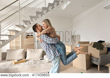 Happy Independent Couple First Time Home Owners Hugging In Living Room On Moving Day. Young Man And