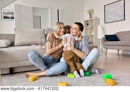 Happy Young Family Couple Having Fun Hugging Cute Small Kid Boy Sitting On Floor In Modern Living Ro