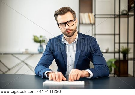 Serious Elegant Business Man Sitting In The Modern Spacious Office Typing On The White Keyboard, Loo