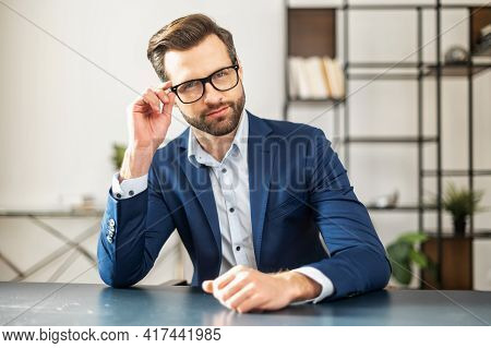 Serious European Man With Bristles In Elegant Suit On An Interview, Holds Hand Near Glasses, Talks A