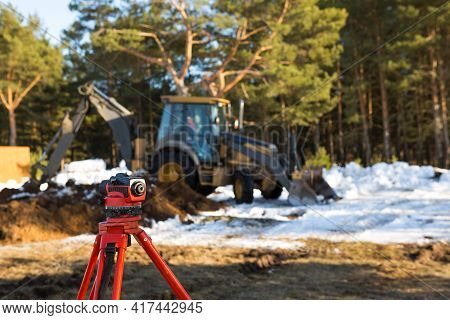 A Geodesic Level Stands In Front Of A Bulldozer For Excavating A Pit At A Construction Site. The Exc