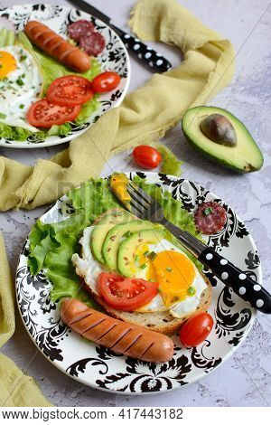 Serving Plate With Appetizing Scrambled Eggs, Tomatoes, Avocado And Sausages On A Gray Background. V