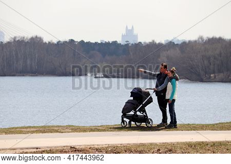 Moscow, Russia - April 2021: Couple With Baby Pram Walking On River Background In Spring City. Famil